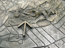 Detail of bronze arrow on tridimensional topographical map